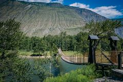 Suspension bridge over the mountain river. The hanging bridge surrounded by lush green trees on the background of mountains and. White clouds on the blue sky royalty free stock photos