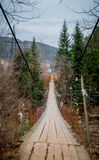 Suspension bridge over mountain river. Journey through the Carpathian mountains in Eastern Europe. Suspension bridge over the spring river Dniester. Rustic old Stock Photos