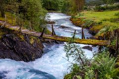 Suspension bridge over the mountain river, Norway. stock photos