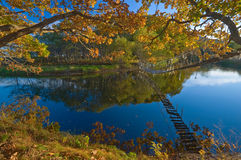 Suspension bridge over the quiet autumn lake-2. Royalty Free Stock Image