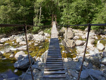 Suspension bridge over river in the Alps Royalty Free Stock Photos