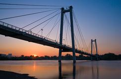 Suspension bridge. Over the river, illuminated by the setting sun Royalty Free Stock Photos