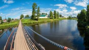 Long suspension bridge over the river. Suspension bridge over the river Msta on a summer day. City Borovichi, Russia stock photo