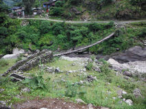 Suspension Bridge over River in Rural Himalayas Stock Photo