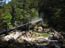 Suspension bridge over river stream Royalty Free Stock Photos