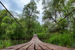 Suspension bridge over river. Stock Photo