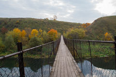 Suspension bridge. Over the river in the village Stock Photography