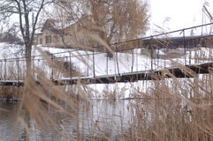 Suspension bridge over a small river against the background of reeds. And snow-covered shores Royalty Free Stock Photos