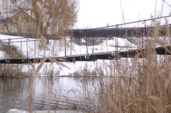 Suspension bridge over a small river against the background of reeds. And snow-covered shores Stock Images