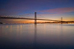 Suspension bridge over Tagus river at nightfall Stock Photography