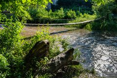 Suspension bridge over a turbulent river, which reflects sunlight. royalty free stock images