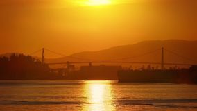 Suspension Bridge And Shipping Area With Beautiful Sunset. Calm water with bridge and mountains bathed in golden evening light stock video