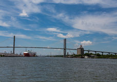 Suspension Bridge Spanning River Over Freighters Stock Photo