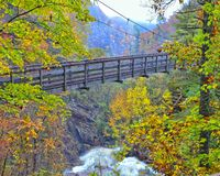 Suspension Bridge at Tallulah Gorge. A wooden suspension bridge over the Tallulah River surrounded by the colors of autumn royalty free stock images
