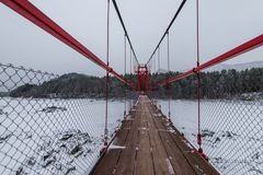 Suspension hanging bridge above winter frozen river royalty free stock image
