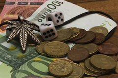 Suspension leaf of marijuana, dice, coins, euro banknotes. Suspension leaf of marijuana, dice, two coins, euro banknotes on a wooden table Royalty Free Stock Photography