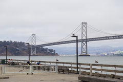 Suspension Oakland Bay Bridge in San Francisco to Yerba Buena Island with downtown during overcast day Royalty Free Stock Photography