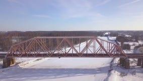Suspension railway bridge for train movement over winter river aerial view. Winter train bridge through frozen river. Drone view stock video