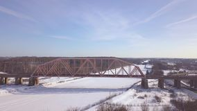 Suspension railway bridge for train traffic over frozen river on winter landscape aerial view. Car traffic on winter. Highway over train bridge drone view stock footage