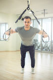 Suspension straps training in modern fitness facility. Young man training with suspension straps in modern gym facility Stock Images