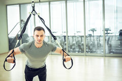 Suspension straps training in modern fitness facility. Young man training with suspension straps in modern gym facility Stock Photography