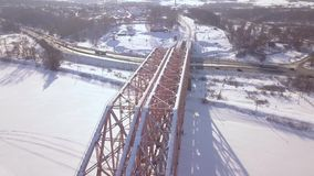 Suspension train bridge through winter river and car traffic on snowy highway aerial view. Railway bridge for train. Movement over frozen river drone view stock video