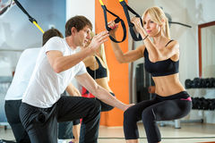 Suspension training with fitness straps. Attractive women doing suspension training with fitness straps Stock Photos