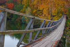 Suspension wooden bridge on river with autumn trees Stock Photography