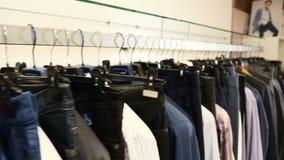 Suspensiones con ropa casual en una alameda Primer: una suspensión para la ropa Suspensiones de ropa Colección de la ropa de dise almacen de metraje de vídeo