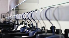 Suspensiones con ropa casual en una alameda Primer: una suspensión para la ropa Suspensiones de ropa Colección de la ropa de dise almacen de video
