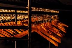 Suspensiones de madera con números en vestuario oscuro imagenes de archivo