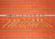 Suspensiones de ropa de madera sobre la pared de ladrillo anaranjada Imagen de archivo libre de regalías