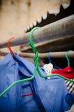 Suspensiones de ropa viejas en la luz del sol Fotos de archivo