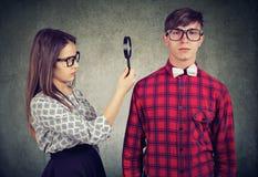 Girl exploring man with magnifying glass royalty free stock photos