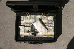 Suspicious briefcase. A black briefcase full of cash, a Bag of White Powder, and a Derringer pistol with extra shells. Lays askew on the ground. Could it be a stock image