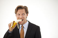 Suspicious businessman eating banana Royalty Free Stock Image