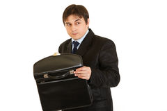 Suspicious businessman holding open briefcase Stock Images