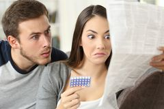 Suspicious couple reading a leaflet after taking contraceptive pills. Sitting on a couch in the living room at home Royalty Free Stock Photos