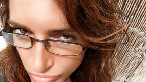 Suspicious Glance. Comic Girl Expression. Close-up of woman face with glasses and expression of suspicion. Fisheye lens Royalty Free Stock Photo