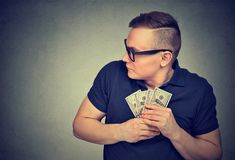 Suspicious greedy man grabbing money. Suspicious greedy young man in glasses grabbing money looking side way Royalty Free Stock Images
