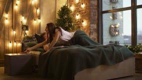 Jealous woman spying on phone of sleepy man in bed
