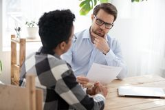 Suspicious male employer doubt about black applicant candidature royalty free stock images