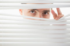 Suspicious male eyes spying through roller blind Royalty Free Stock Images