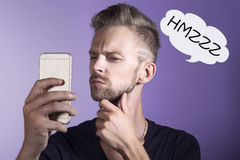 Suspicious man checking his mobile phone. Man looking doubtful to his phone stock photos