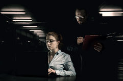 Suspicious man controls work of a woman. Suspicious men controls work of a women in a dark room. The concept of hard work under pressure royalty free stock photos