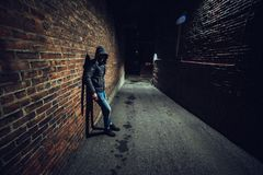 Suspicious man in dark alley waiting for something. Suspicious man in dark alley waiting for something there royalty free stock photo