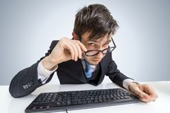 Suspicious man in glasses is working with computer and looking at you Stock Photo