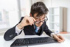 Suspicious man in glasses is working in office and looking at you Royalty Free Stock Photos