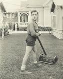 Suspicious man  with a push reel lawn mower Stock Photo