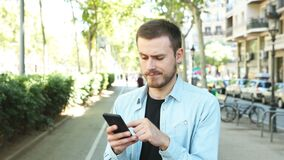 Suspicious man using phone looking at you stock footage